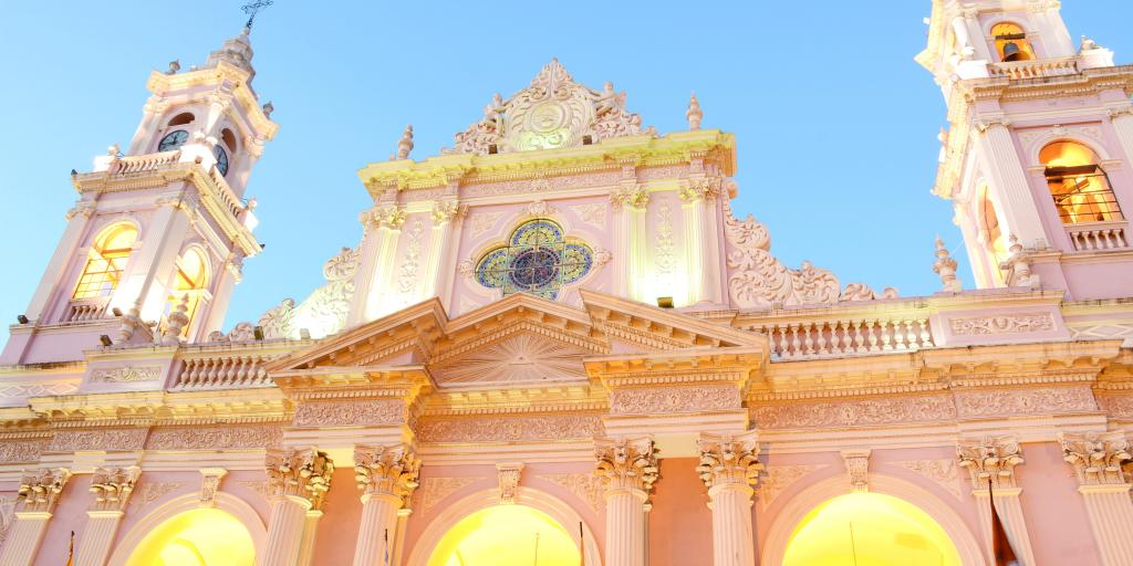 A close up of the baby pink exterior of Salta Cathedral with lights in the arches