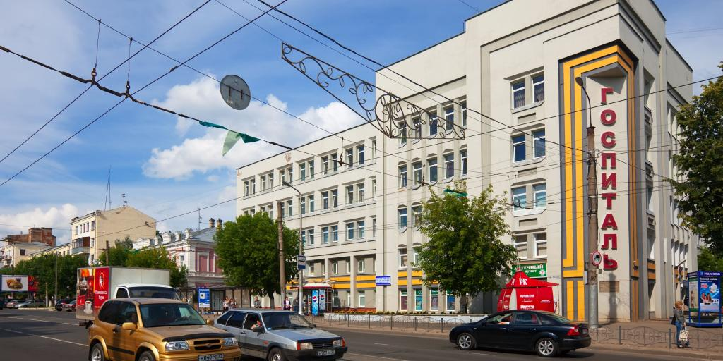 A street in Ivanovo, Russia, with cars going past a big rectangular grey building