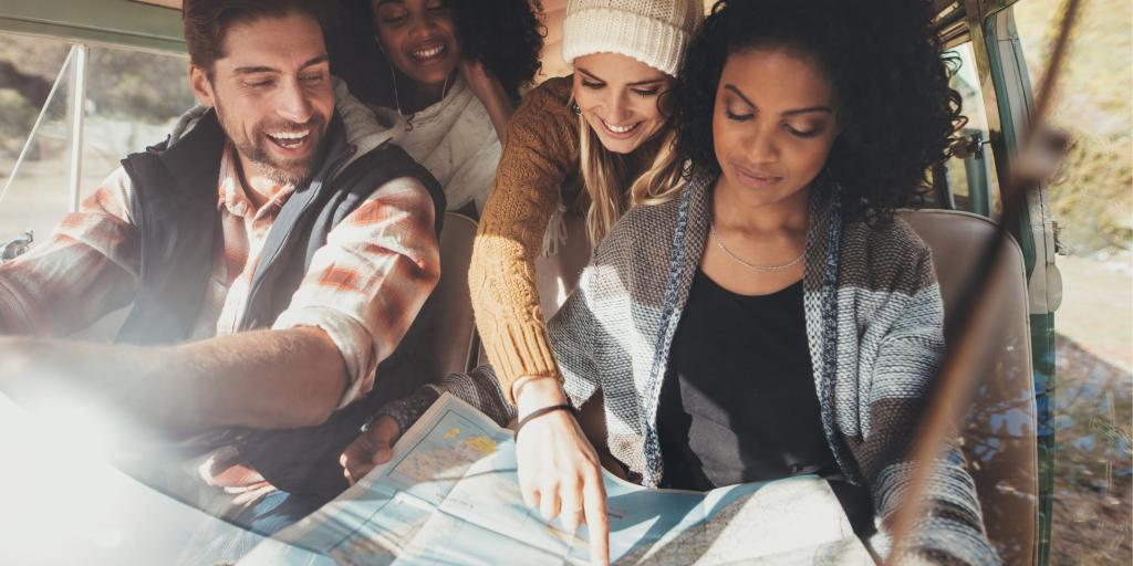 Friends looking at a map on their road trip