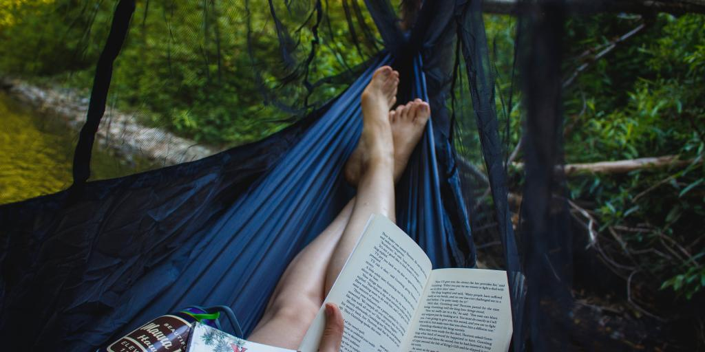 The feet of someone reclining in a hammock in a wooded area, with a book, a magazine and a water bottle all in view