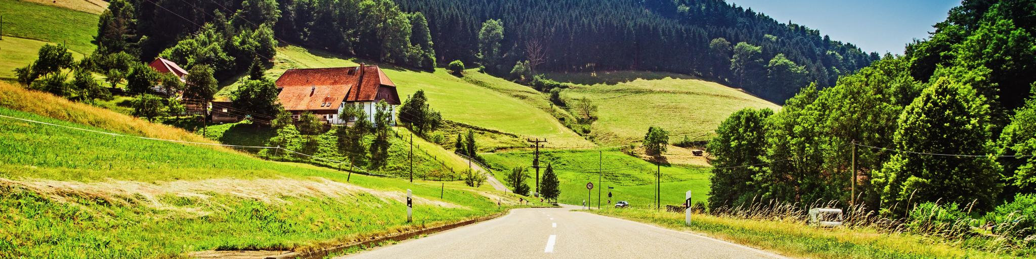 Cars on a German road with mountains and lush green hills in the background