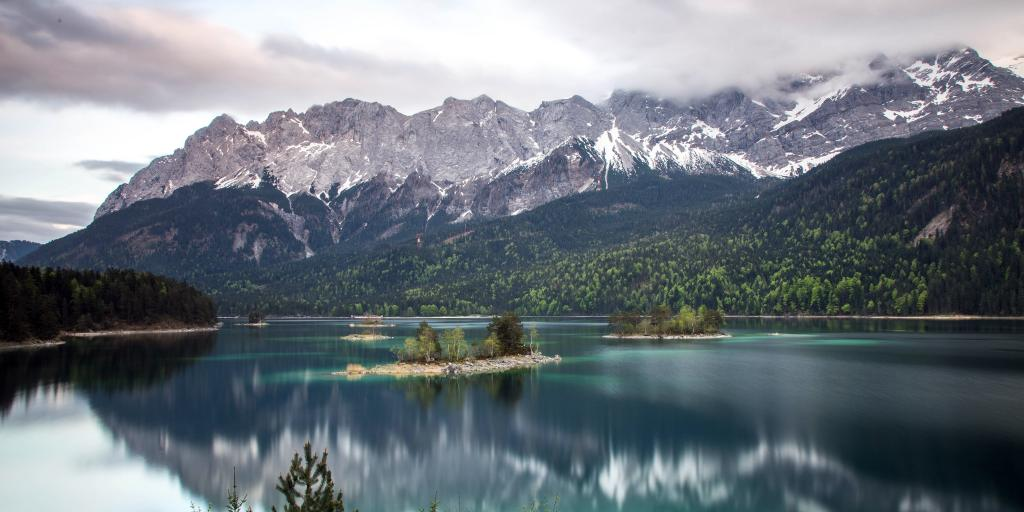 Snow-capped mountains reflect on the surface of Lake Eibsee in Garmisch-Partenkirchen, Bavaria