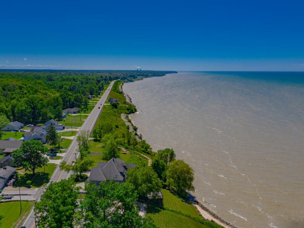 An aerial view of green forest-like trees and Lakeside road along Lake Erie Coastline in a good weather