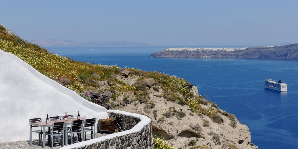 A table with wine bottles on top looks over the cobalt blue sea in Santorini