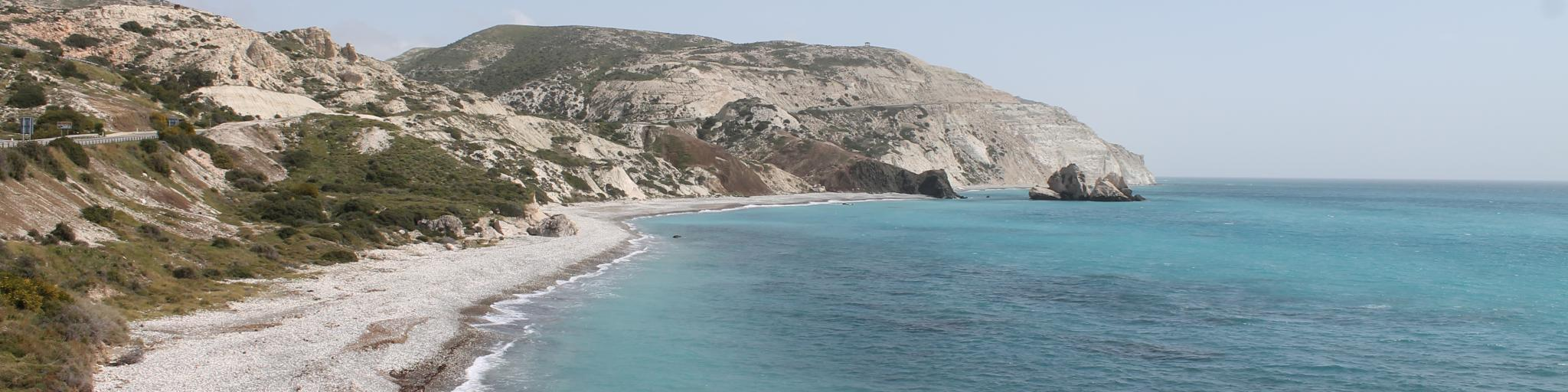 Turquoise water laps against the pebble beach at Paphos, Cyprus