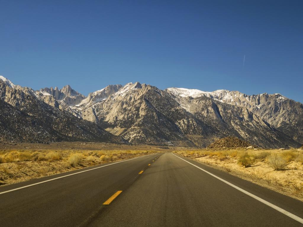 The iconic California State Highway 395 in Owens Valley on Eastern Flanks of Sierra Nevada Mountains with distant Mount Whitney on Horizon.