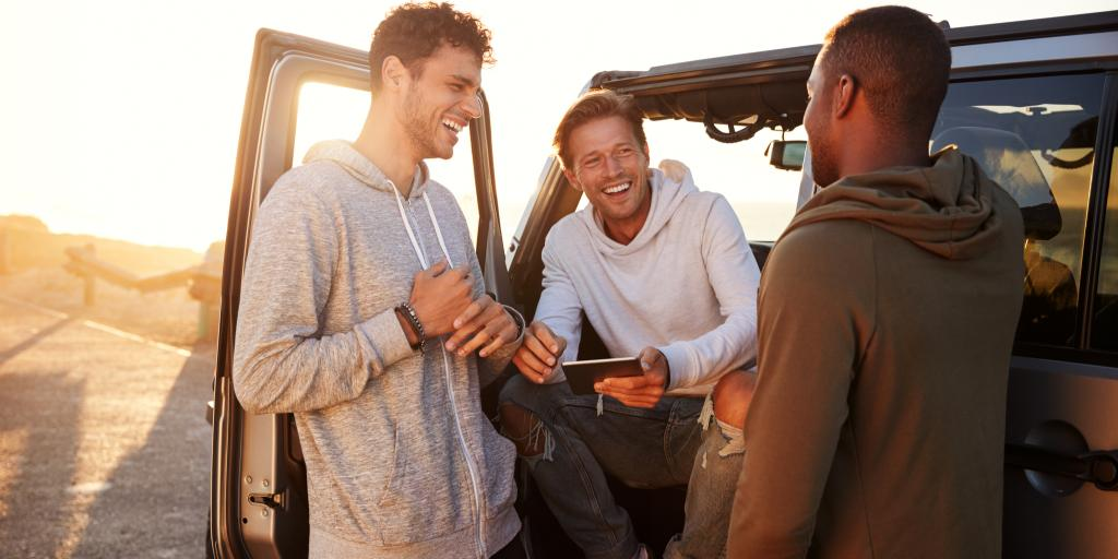 Three male friends laughing with each other on a road trip