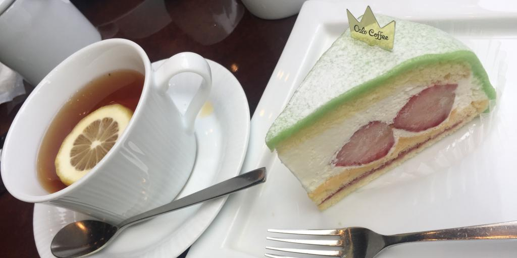A cup of tea and a green slice of cake at Oslo Coffee in Tokyo