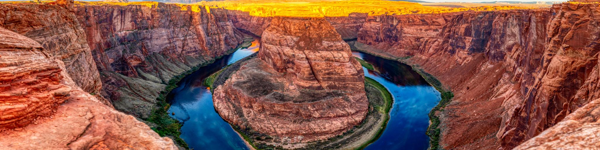 The light of sunrise illuminating Horseshoe Bend, made of Navajo sandstones with clear blue water running along the Grand Canyon