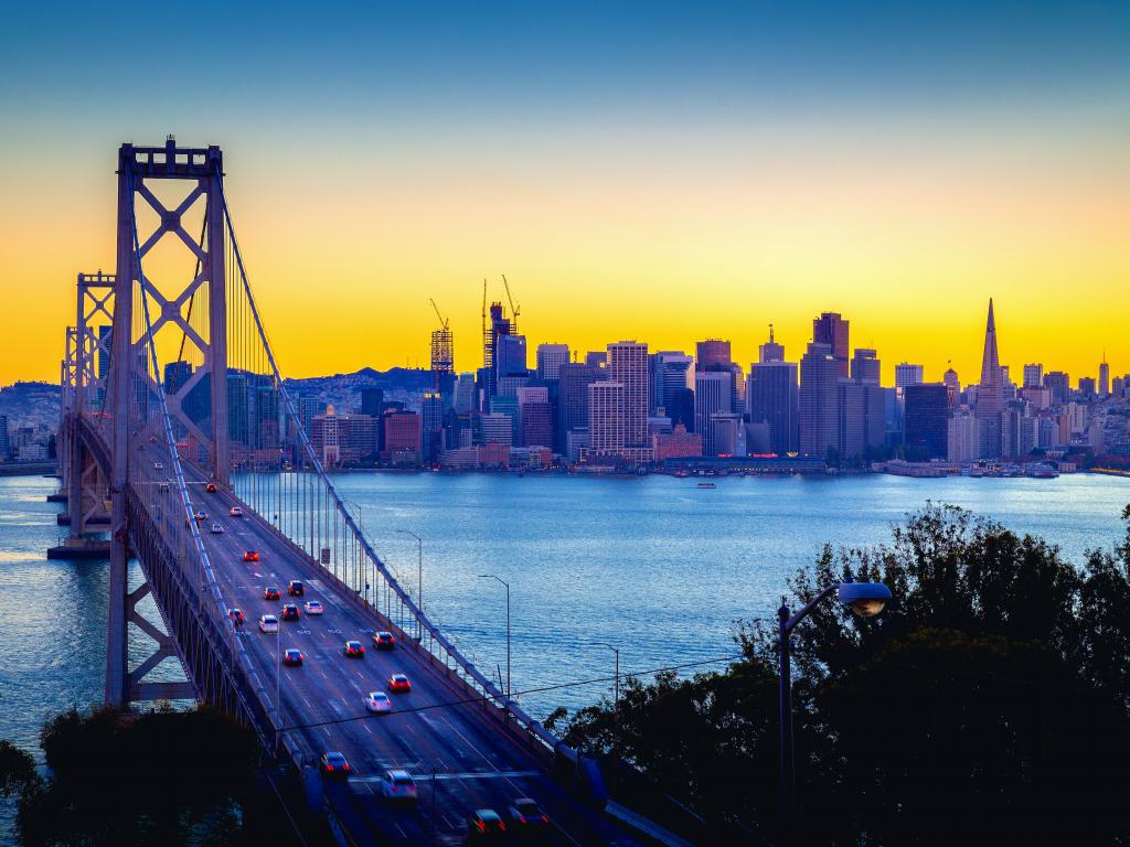 A beautiful twilight golden sunset glow of summer illuminating the skyline of San Francisco and a panoramic view of the famous Oakland Bay Bridge with cars driving along the bridge (Interstate 80)