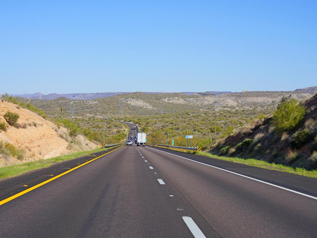 Interstate 17 at Arizona with several cars and trucks driving along the highway taking in the view of the mountains and green trees