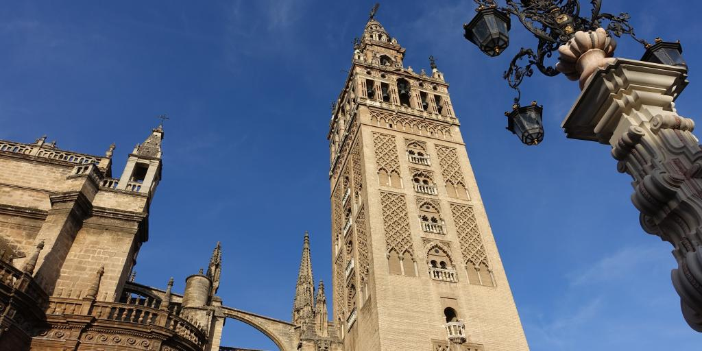 The La Giralda bell tower in Seville stands tall next to the cathedral