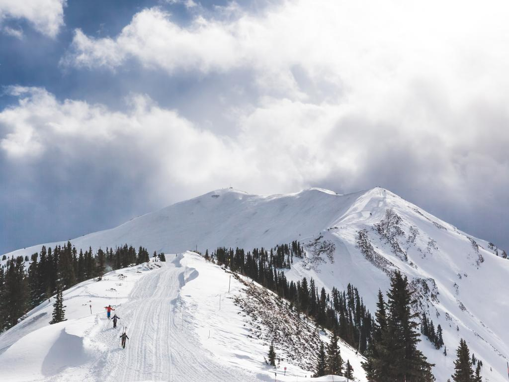 A group of skiers hiking up to the Aspen Highlands Bowl