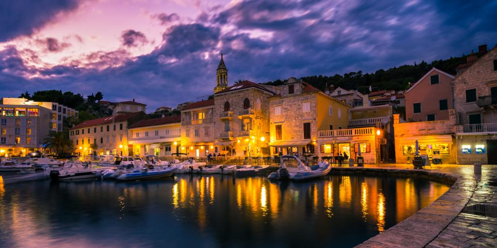 Harbour of Hvar in the evening with boats and lights reflecting on the water