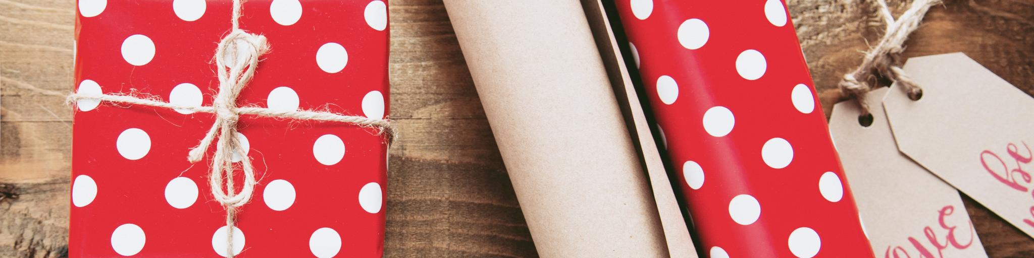 Red and white polka dot wrapping paper with a string bow and two rolls of wrapping paper - one polka dot, one brown parcel paper