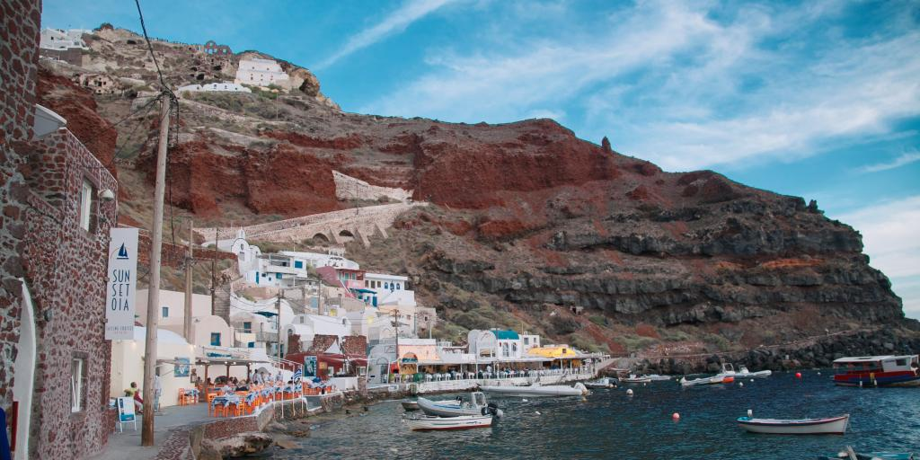 Boats floating in Amoudi Bay, with red volcanic cliffs in the background