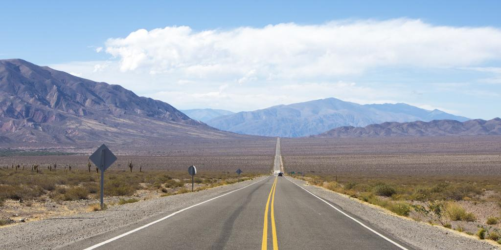 Long stretch of straight road on Route 40 with mountains behind near Cafayate