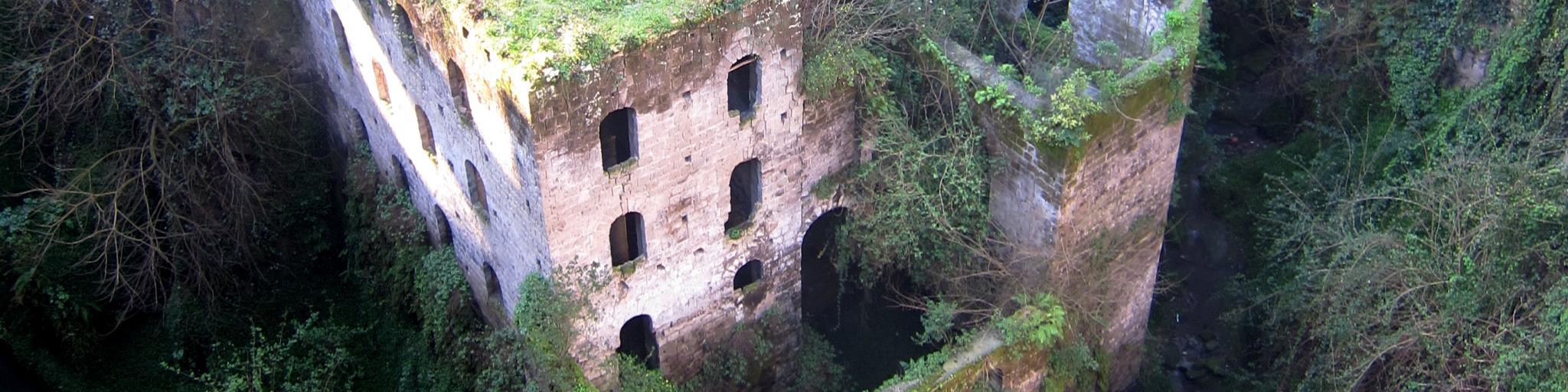 Abandoned buildings are overgrown by greenery in the Valley of the Mills