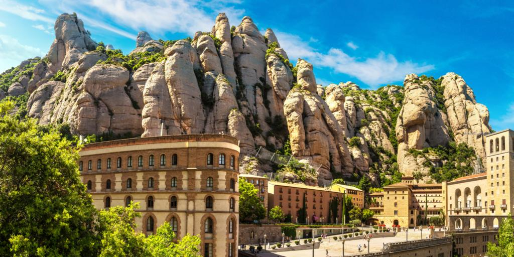 The stunning Montserrat Monastery sits on a craggy mountain with a blue sky above