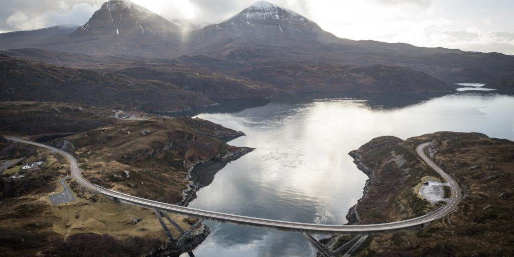 An aerial view of the curved Kylesku Bridge, Scotland, with two munros in the background