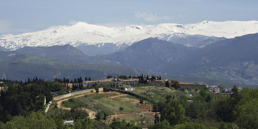 A town in Spain with the snow-capped peaks of the Sierra Nevada mountain range in the background
