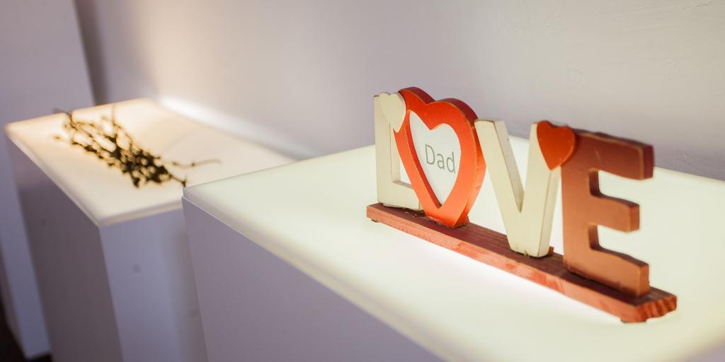 A photo frame spelling out the word LOVE with a piece of paper saying 'dad' inside
