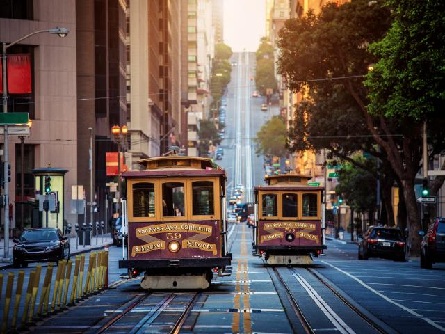 Traditional San Francisco cable cars passing each other on one of the city's steep streets.