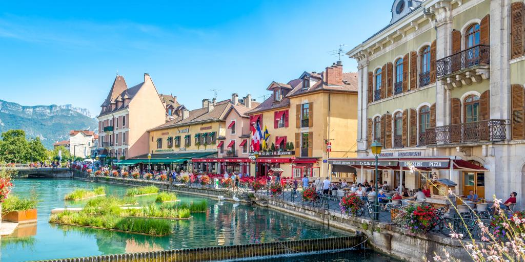 Restaurants and cafes alongside a turquoise canal on a sunny day in Annecy, France