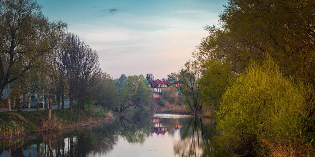 A house in the distance with its reflection visible in the water below it, surrounded by trees, in Suzdal, Russia