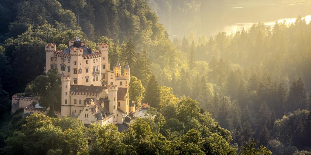 Hohenschwangau Castle in Fussen, Bavaria, peeking out of the surrounding forest, with a ray of sunlight hitting it