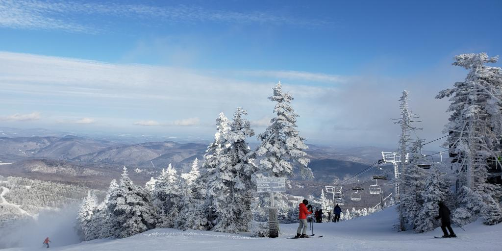 Two skiiers standing at the top of a piste in Killington, Vermont, surrounded by snowy trees and with a chair lift travelling overhead