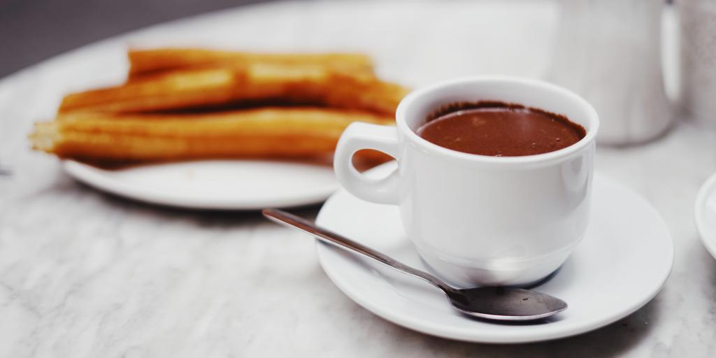 A cup of hot dipping chocolate on a table next to a plate of churros