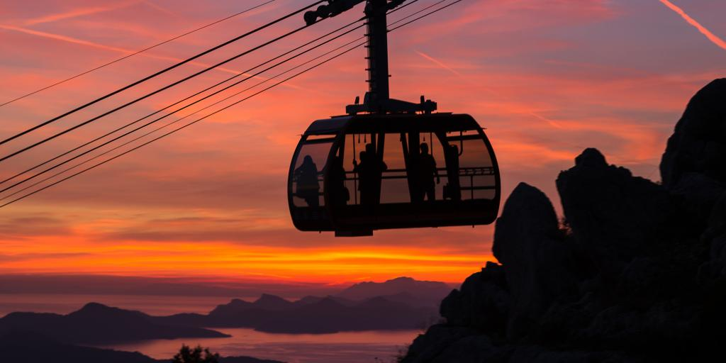 A silhouette of the Dubrovnik Cable Car at sunset against an orange and pink sky