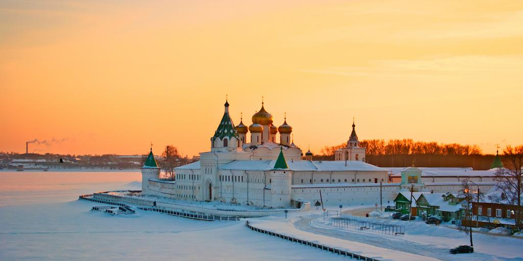 The Ipatiev Monastery in Kostroma, Russia, shown in winter at sunset, with the lake in front frozen and the gold domes visible