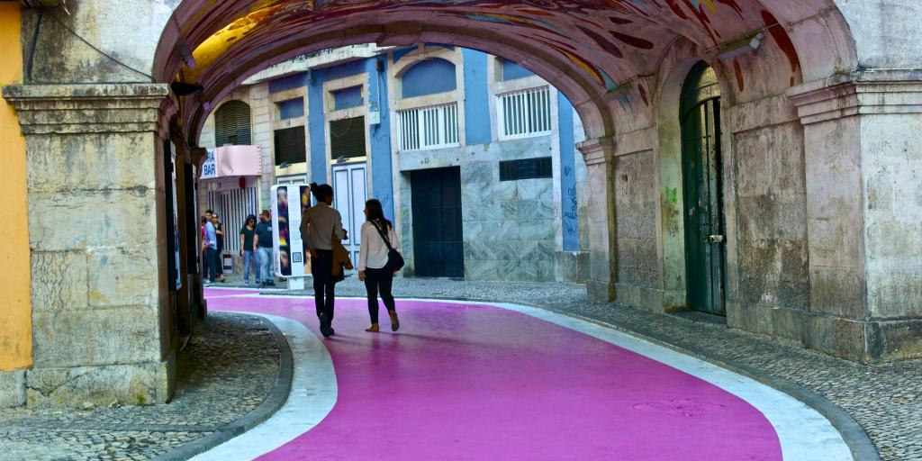 People walking under a tunnel along Lisbon's famous Pink Street