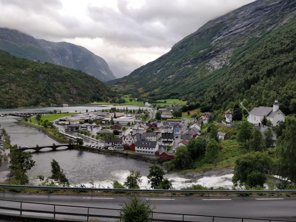A waterfall rushes down past the town of Hellesylt in Norway