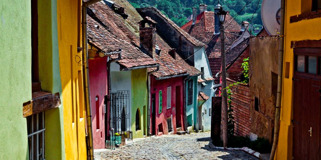 A cobbled street lined with pretty coloured houses in Sighisoara, Romania