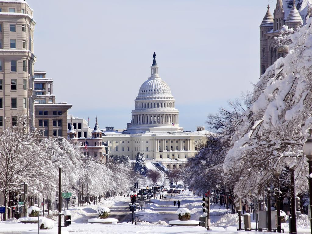 A snowy winter scene in Washington D.C. with a street leading to the U.S. Capitol