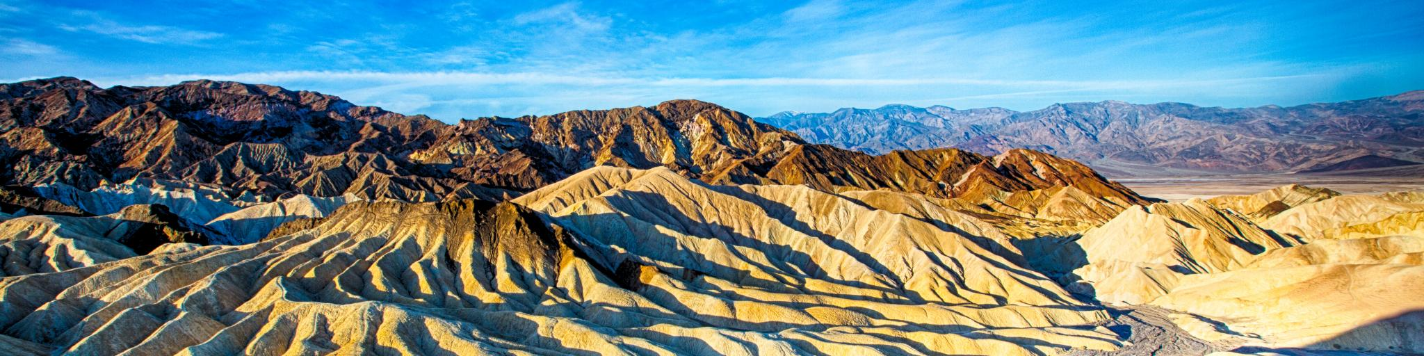 An image that shows how the Zabriskie Point in Death Valley National Park, California, USA looks during sunrise in a clear and bright sky.