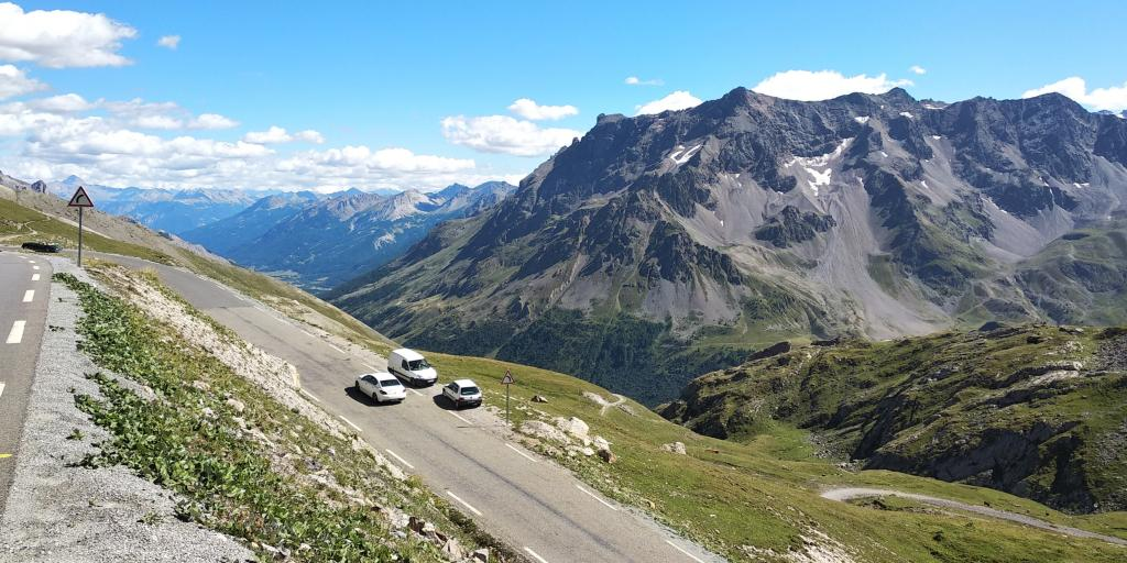Cars parked on the side of the road on the Col de la Bonette, France with mountain peaks in the background