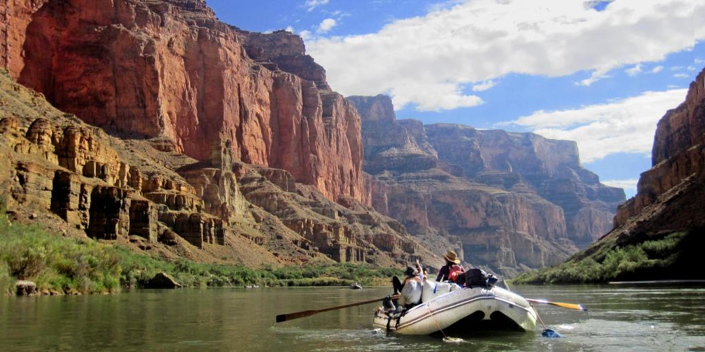 A raft boat floats down the Colorado River in the Grand Canyon
