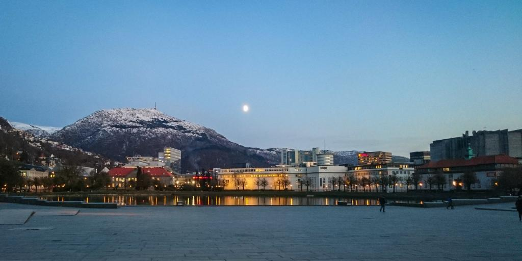 The moon sets over the city of Bergen and Mount Ulriken in Norway