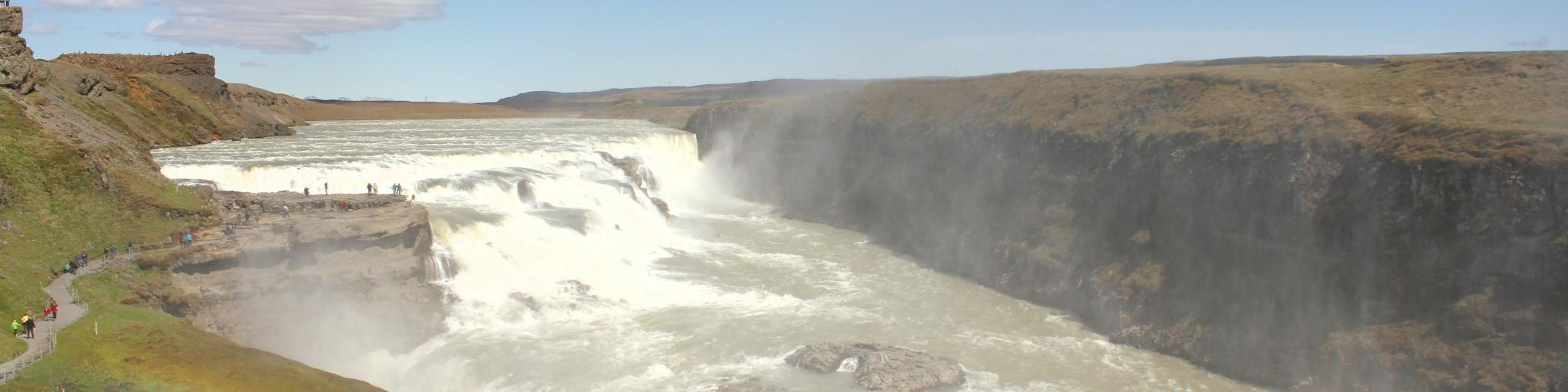 A rainbow forms over Gulfoss waterfull on a sunny day