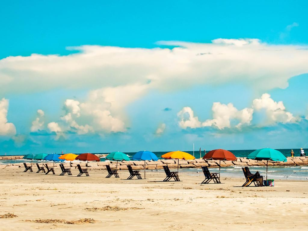 Colorful umbrellas and sun loungers on the beach of Galveston Island, Texas