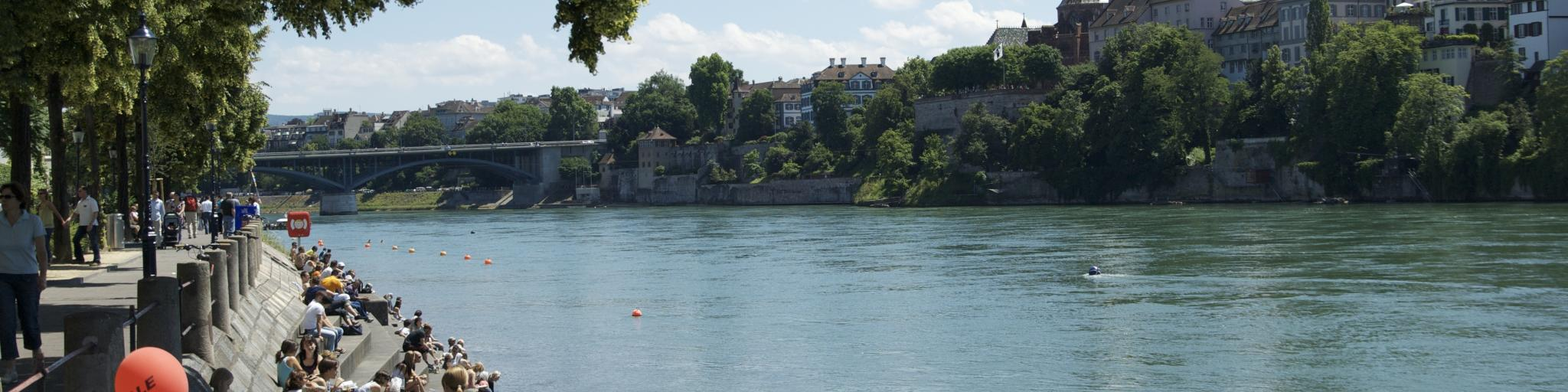 People sitting on the banks of the Rhine River in Basel