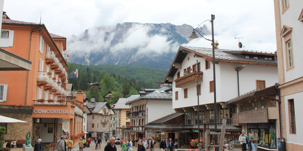 Shoppers and visitors walk through the pedestrian ski town centre of Cortina d'Ampezzo, Italy