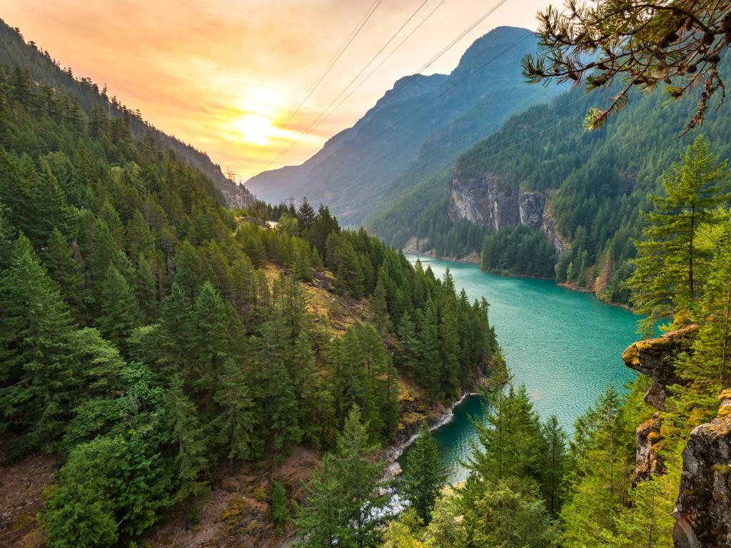 Diablo Lake in North Cascades National Park at sunrise surrounded by mountains and forest.