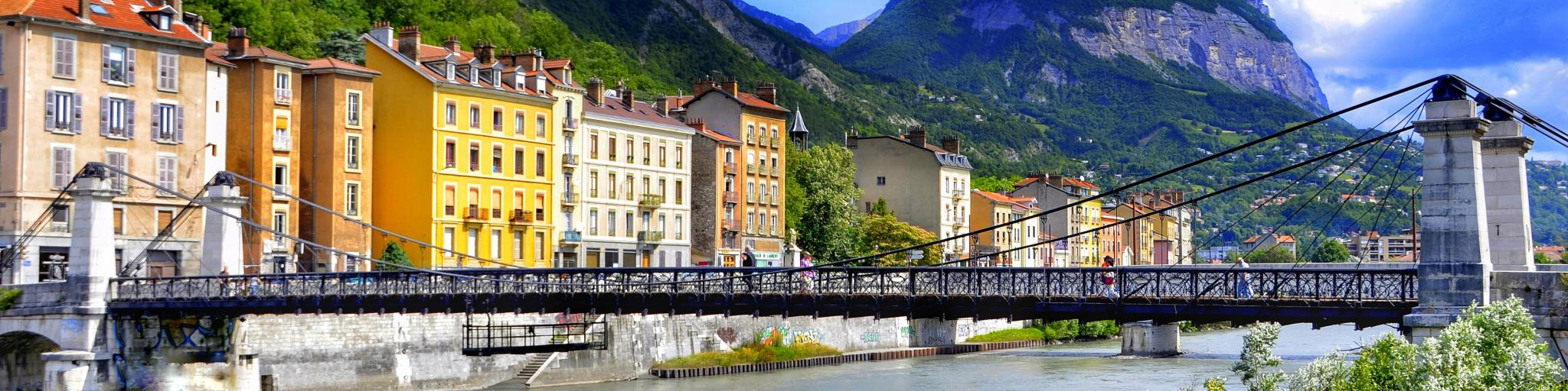 A view of a bridge over the river in Grenoble with colourful houses and mountains in the background