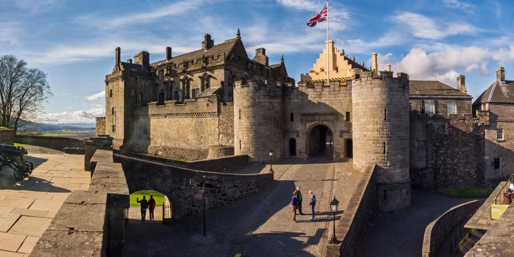 People walk up the bridge to Stirling Castle on a blue sky day in Scotland