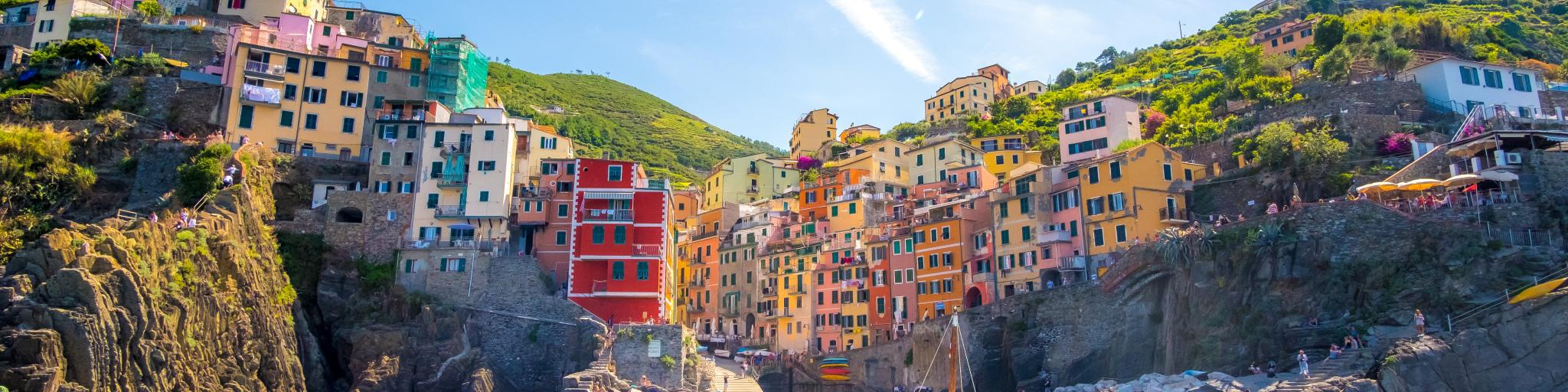 Colourful buildings and a boat on the sea in Riomaggiore, Italy